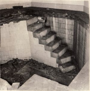 "These photographs are of the sunken baths, a feature of the 1818 building. They were revealed when repairs when necessary to defective floor joists in the dormitory which had been created using the space above the bath when it ceased to be used. This was situated on the South East corner of Ward 18 octagon. When uncovered the tiles were in perfect condition, not at all ""crazed"". After these photographs were taken, the space was filled in with sand and a concrete floor laid.(circa 1965)"