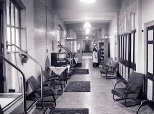 "Ward 27 looking towards what later became stage IV of the reconstruction programme and when reopened, Gorse Ward. The dorm on the left had been upgraded locally. On the right in the large opening was a door leading to the rear stairs down to the ""Female Central"" and Nursing Officers' Residential Quarters, Dining Room, Kitchens etc"